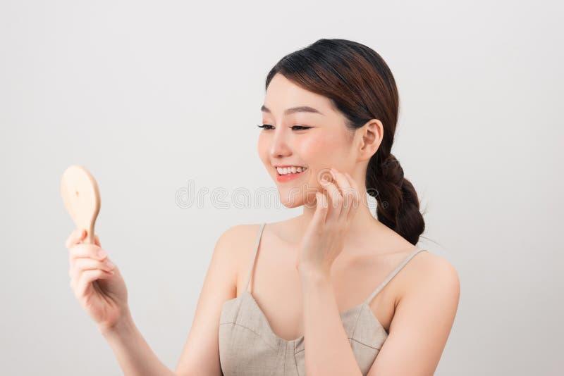 Ung asiatisk spegel f?r leende och f?r blick f?r kvinna f?r hudomsorg arkivfoto
