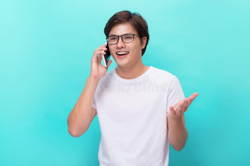 Ung asiatisk stilig affärsman som smilling och använder hans smartpho royaltyfria foton