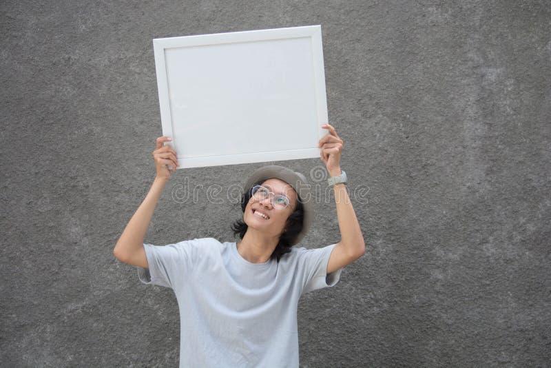 Ung asiatisk student med exponeringsglas och fedorahattanseendet som rymmer det vita brädet och ler, tomt brädebegrepp arkivbild