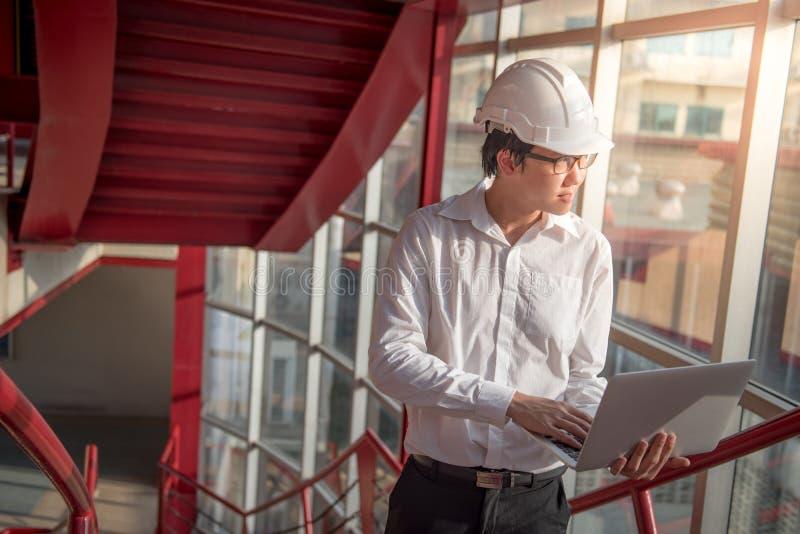 Ung asiatisk tekniker eller arkitekt som arbetar med bärbara datorn arkivfoton