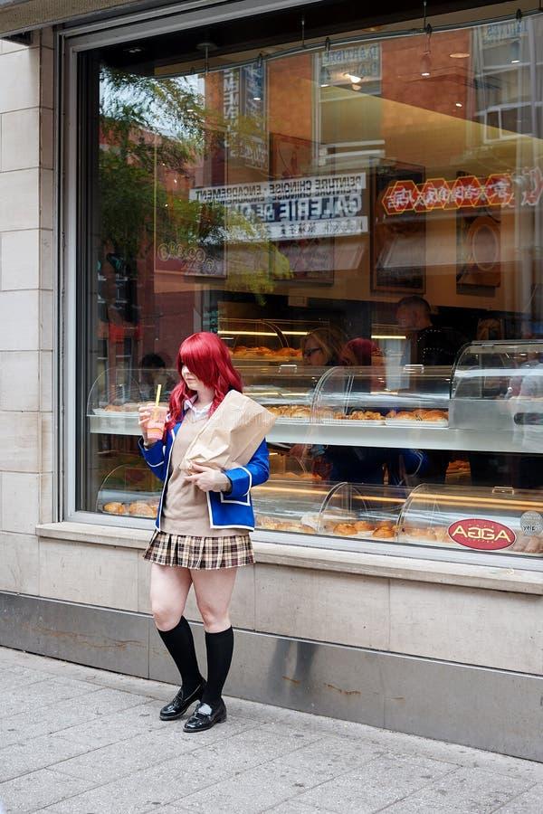 Ung asiatisk tonårs- skolflicka som framme poserar av ett kafé arkivfoton