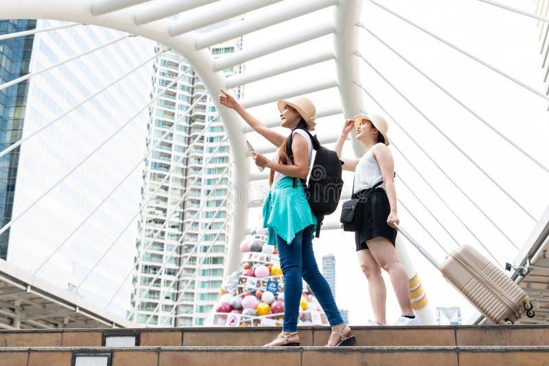 Ung asiatisk turist- kvinna som pekar in i avstånd medan hennes se för vän royaltyfria foton