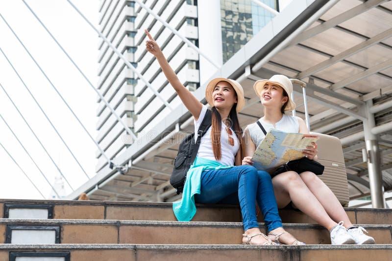 Ung asiatisk turist- kvinna som pekar in i avstånd medan hennes vän som ser med att le framsidor royaltyfri bild