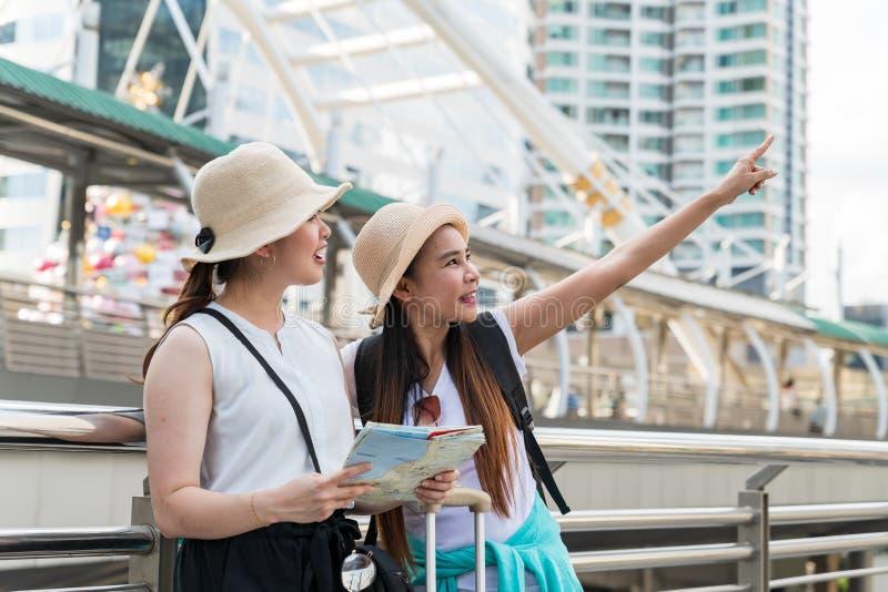 Ung asiatisk turist- kvinna som pekar på byggnaden medan hennes vän som ser och rymmer en översikt arkivfoto