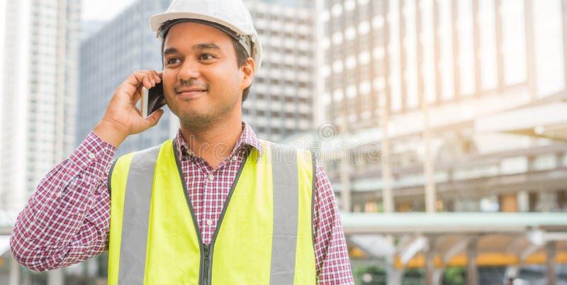 Ung asiatisk väg-och vattenbyggnad som talar på telefonen på konstruktionsbyggnadsbakgrund royaltyfri foto