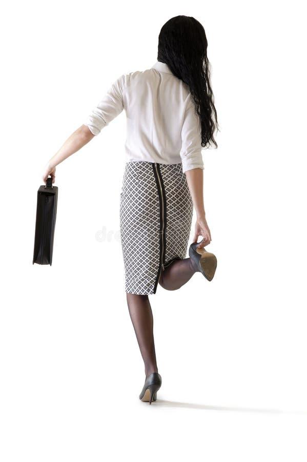 Ung attraktiv affärskvinna som justerar hennes shoees arkivfoto