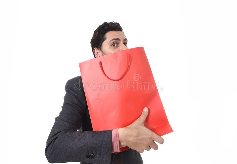 Ung attraktiv affärsman i den hållande shoppingpåsen för spänning som ser girig efter köpande fynd arkivbilder