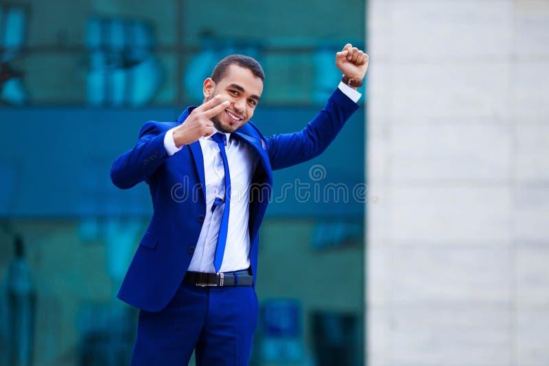 Ung attraktiv affärsman i dräkt som firar framgång, demon royaltyfri foto