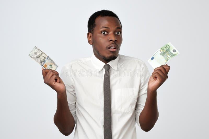 Ung attraktiv afrikansk man som rymmer USA valuta och eurovaluta som avgör vilket för att välja arkivbild