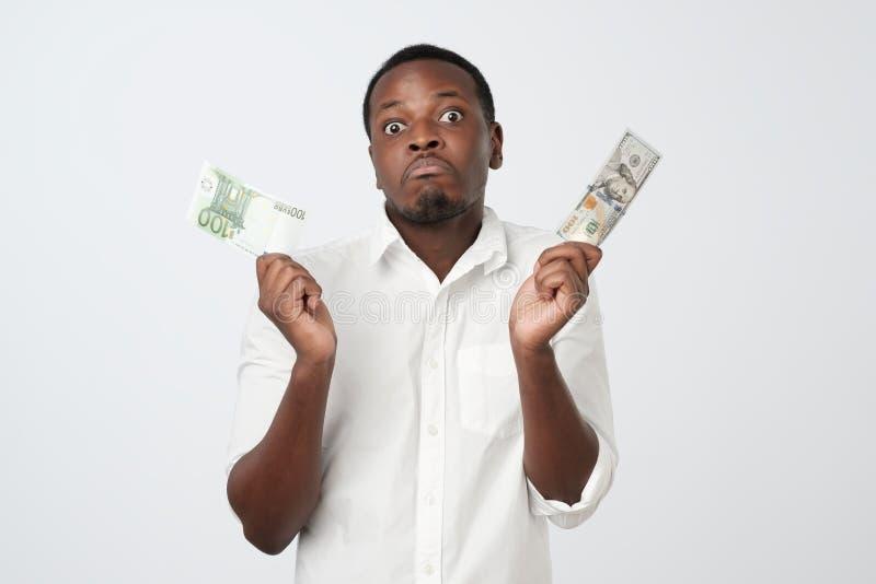 Ung attraktiv afrikansk man som rymmer USA valuta och eurovaluta som avgör vilket för att välja royaltyfri bild