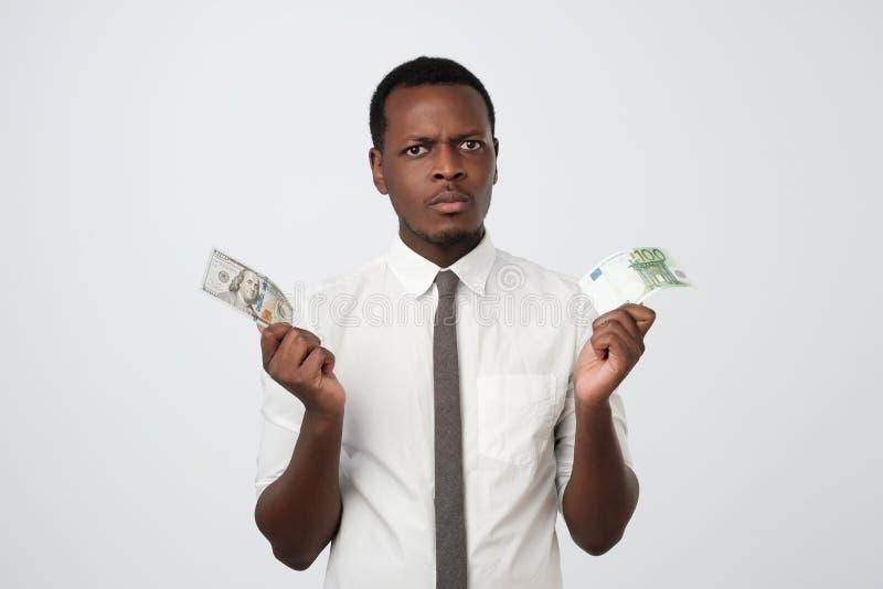Ung attraktiv afrikansk man som rymmer USA valuta och eurovaluta som avgör vilket för att välja royaltyfri fotografi