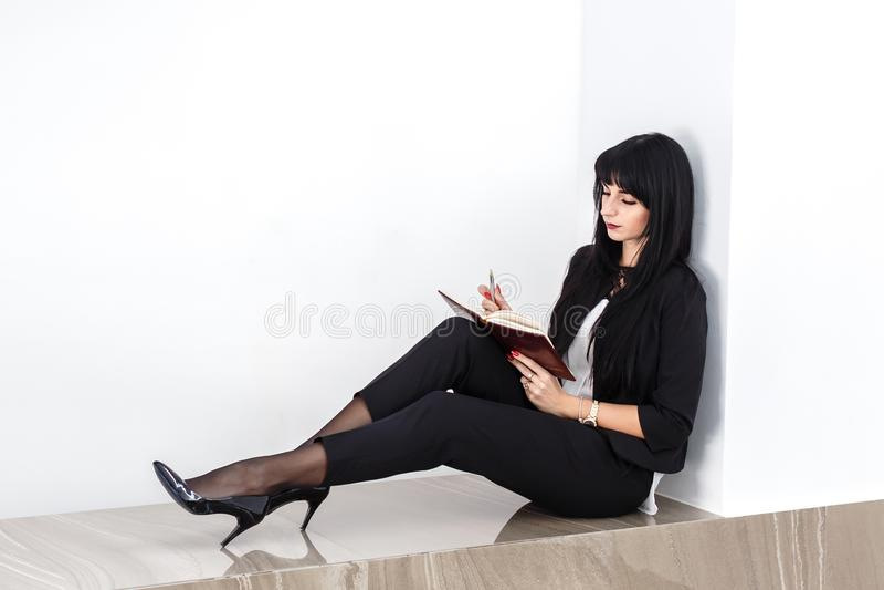 Ung attraktiv allvarlig iklädd brunettkvinna en svart affärsdräkt som sitter på ett golv i ett kontor som läser i en anteckningsb arkivfoton
