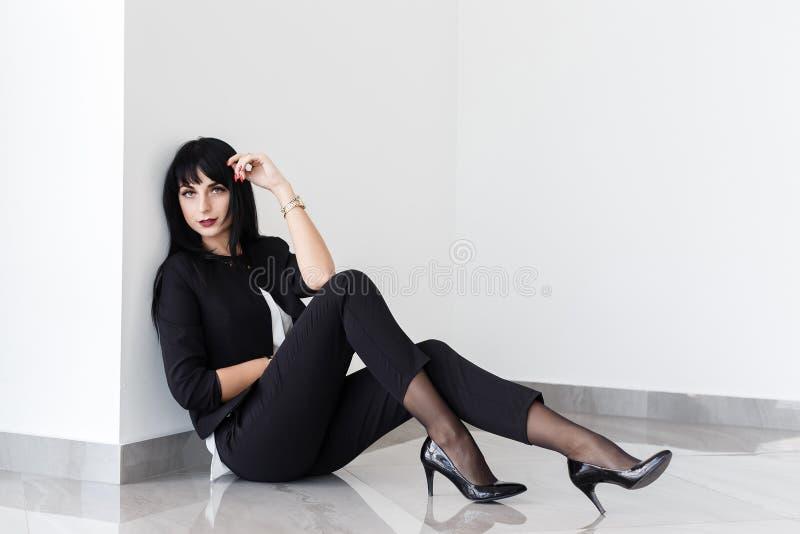 Ung attraktiv allvarlig iklädd brunettkvinna en svart affärsdräkt som sitter på ett golv i ett kontor med vita väggar arkivfoton