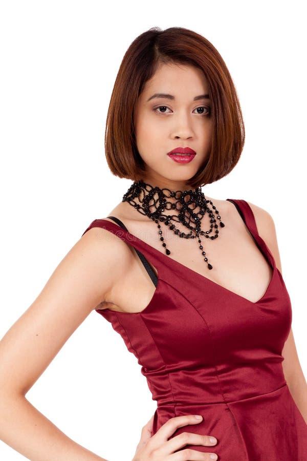 Ung attraktiv asiatisk kvinna med röda isolerade kanter och smycken royaltyfria foton