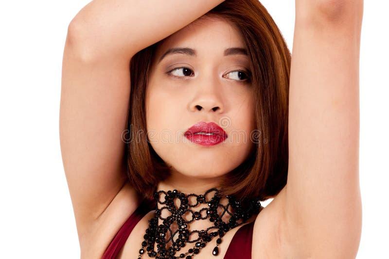 Ung attraktiv asiatisk kvinna med röda isolerade kanter och smycken royaltyfri foto