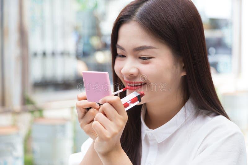 Ung attraktiv asiatisk kvinna som sätter på makeup royaltyfri bild