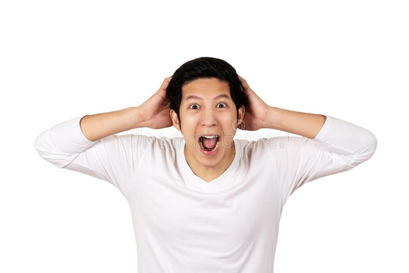 Ung attraktiv asiatisk man i den tillfälliga vita skjortan som ser kameran med den förbluffade, spännande eller chockade framsida fotografering för bildbyråer