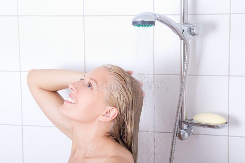Ung attraktiv blondiekvinna som har en dusch arkivbild