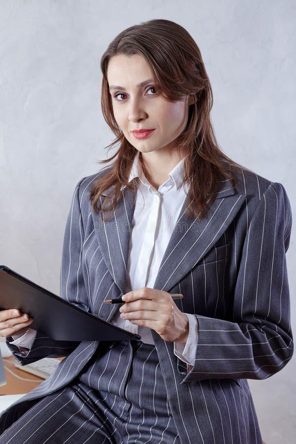 Ung attraktiv brunettaffärskvinna med penn- och skrivplattablickar på kameran som ler Klassisk randig mandräkt, vit shir royaltyfri foto