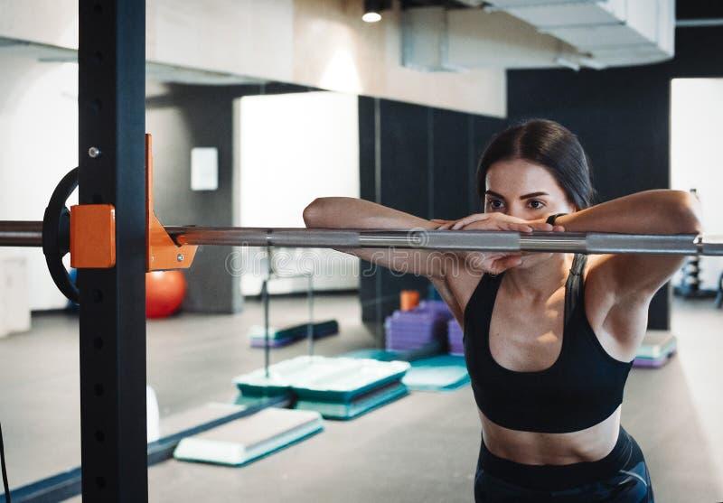 Ung attraktiv brunettflicka som enlacing hennes sportskor efter praktiserande genomkörare- och crossfitutbildning på matt blå yog arkivbilder