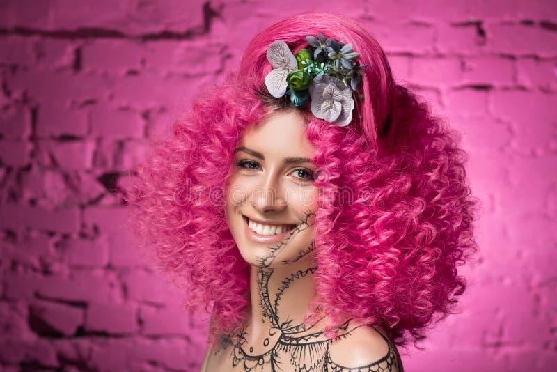 Ung attraktiv caucasian flickamodell med lockigt ljust rosa hår för afrikansk stil, tatuerad framsida och hals och blommor som  royaltyfri fotografi