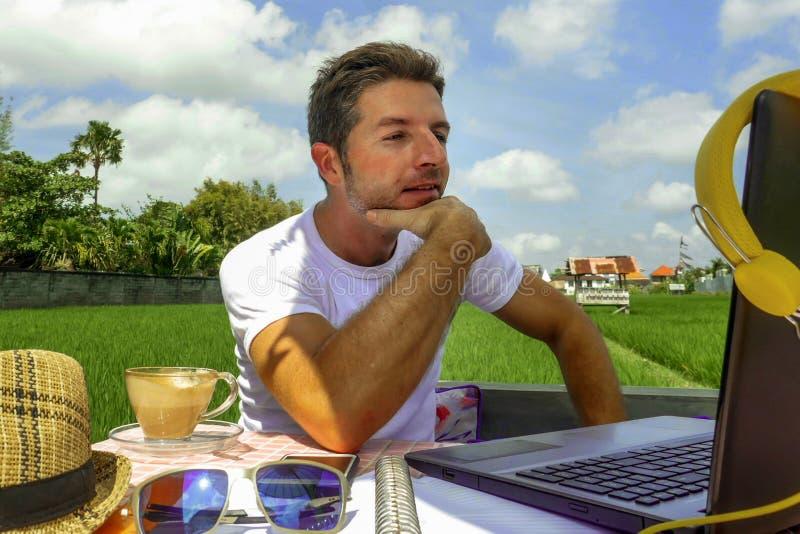 Ung attraktiv digital nomadman som utomhus arbetar på linje med den bärbar datordatoren och mobiltelefonen som freelancer och obe arkivbild