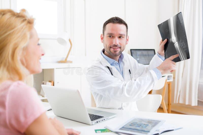 Ung attraktiv doktor som analyserar röntgenstrålen med patienten royaltyfri bild