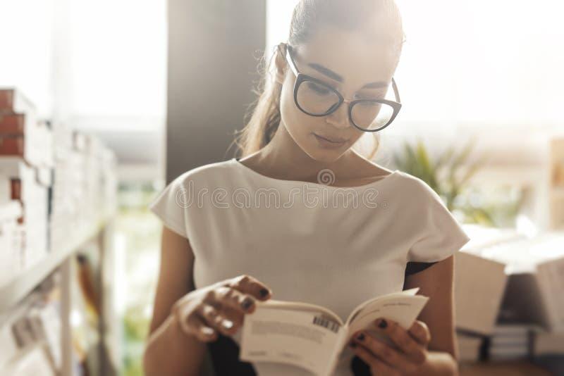 Ung attraktiv eftertänksam kvinnaläsebok i ett boklager Bekläda beskådar arkivbild