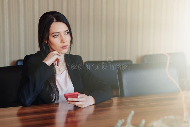 Ung attraktiv emotionell flicka i affärsstilkläder som i regeringsställning sitter på skrivbordet med telefonen eller åhörare royaltyfria foton