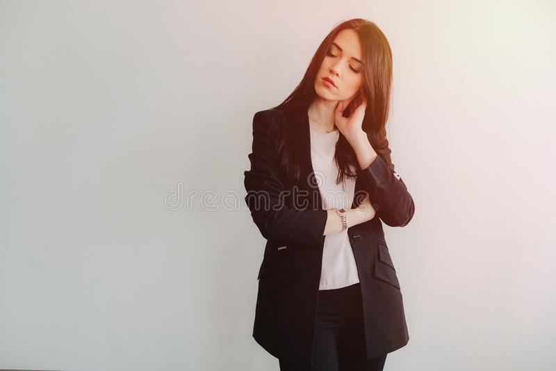 Ung attraktiv emotionell flicka i aff?r-stil kl?der p? en vanlig vit bakgrund i ett kontor eller ?h?rare arkivbilder