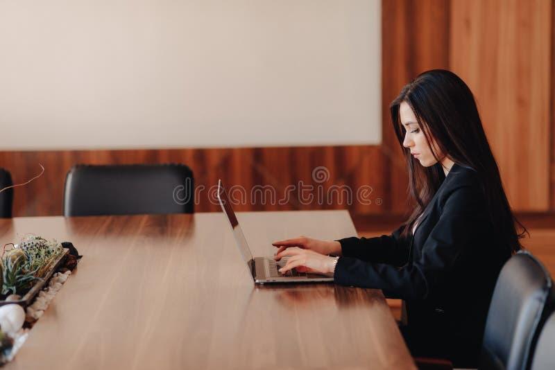 Ung attraktiv emotionell flicka i aff?r-stil kl?der som sitter p? ett skrivbord p? en b?rbar dator och en telefon i kontoret elle royaltyfria foton