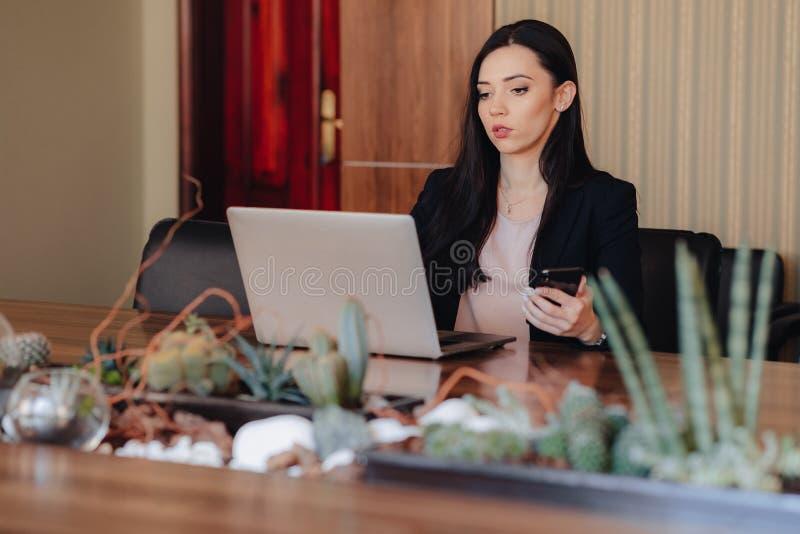 Ung attraktiv emotionell flicka i aff?r-stil kl?der som sitter p? ett skrivbord p? en b?rbar dator och en telefon i kontoret elle arkivfoto
