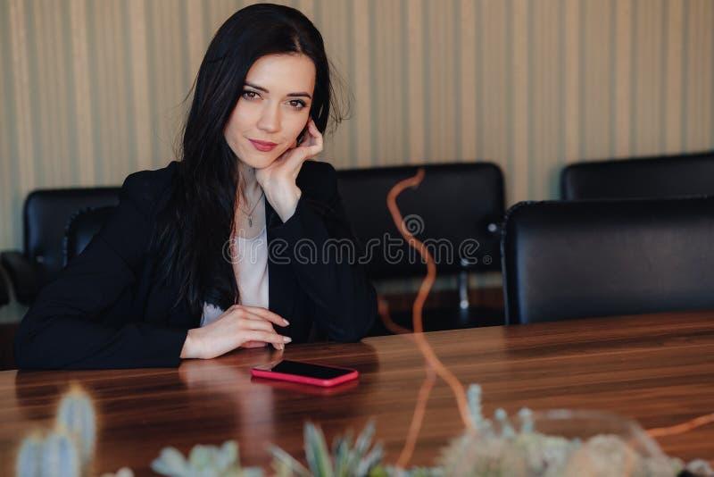 Ung attraktiv emotionell flicka i aff?rsstilkl?der som i regeringsst?llning sitter p? skrivbordet med telefonen eller ?h?rare royaltyfri fotografi