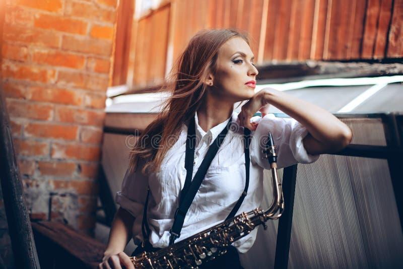 Ung attraktiv flicka i den vita skjortan med en saxofon - som är utomhus- i gammal stad Sexig ung kvinna med saxofonen som tänker arkivfoton