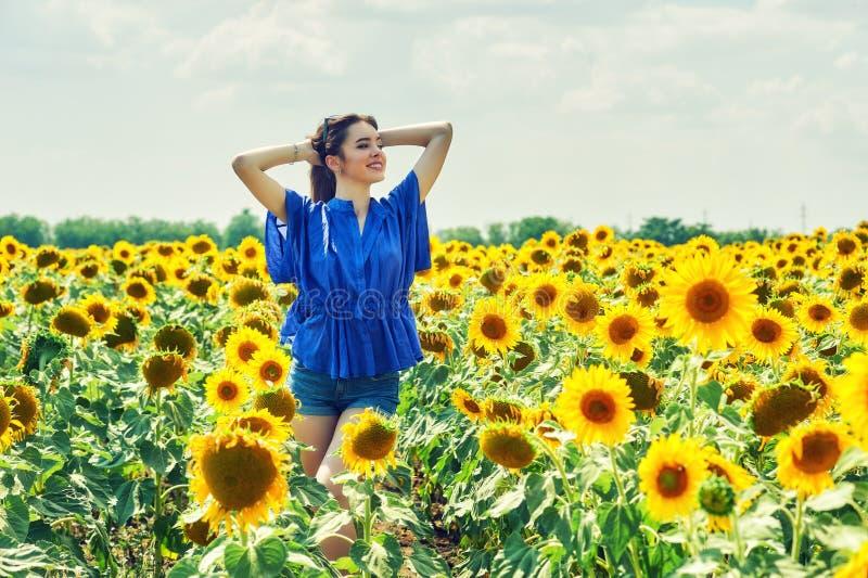 Ung attraktiv flicka i fältet med solrosor royaltyfri fotografi