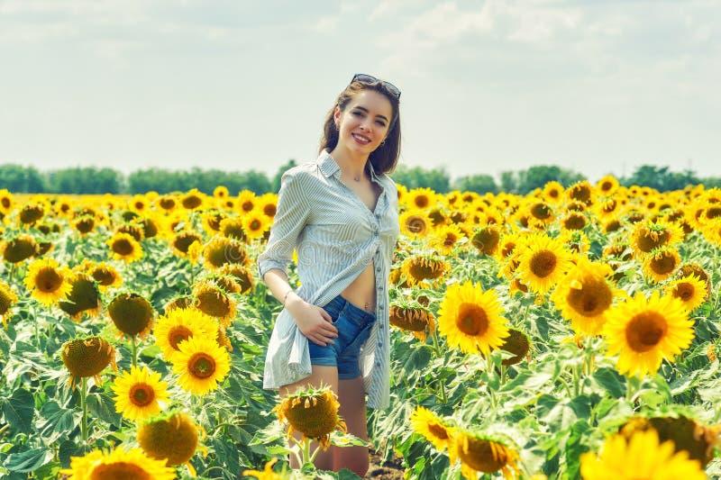 Ung attraktiv flicka i fältet med solrosor royaltyfri bild