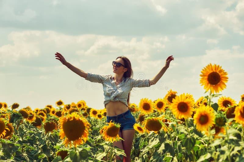 Ung attraktiv flicka i fältet med solrosor arkivbilder