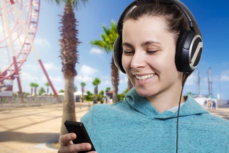 Ung attraktiv flicka med en spelare på en stadsgata på en klar solig dag som lyssnar till musik royaltyfria foton