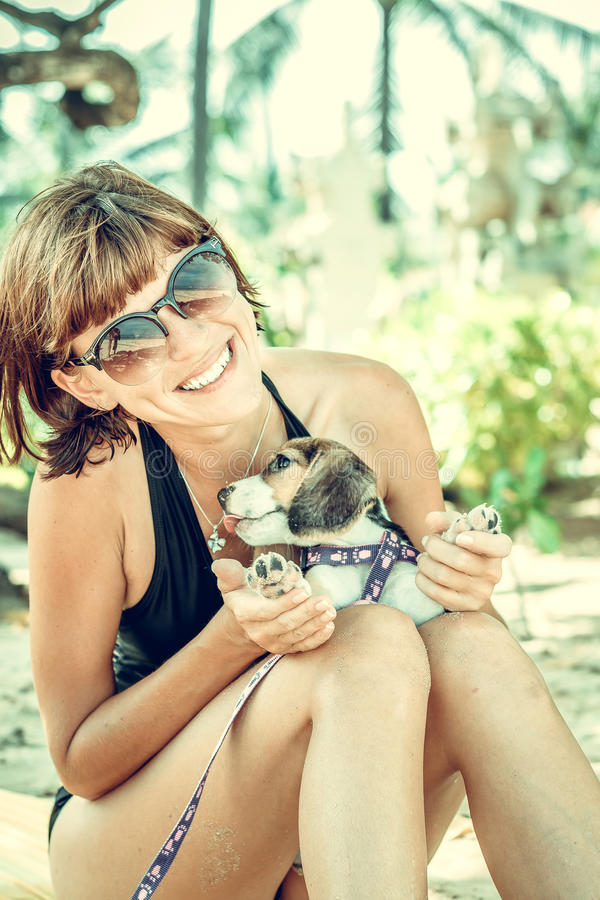 Ung attraktiv flicka med hennes beagle för älsklings- hund på stranden av den tropiska ön Bali, Indonesien lyckliga ögonblick royaltyfri foto