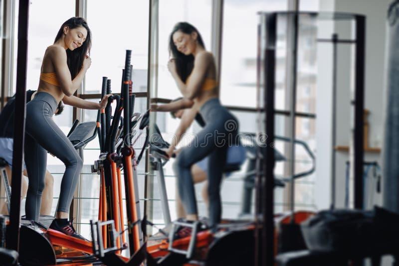 Ung attraktiv flicka p? idrottshallen p? motionscykelen, kondition och yoga arkivfoto