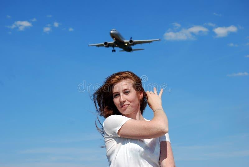 Ung attraktiv flicka som ler och poserar på bakgrunden av nivån som går att landa på bakgrunden av den blåa himlen royaltyfri foto