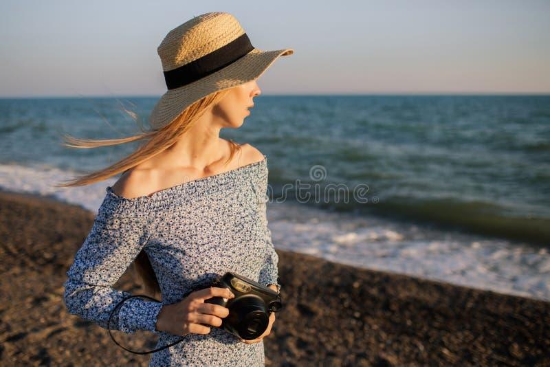 Ung attraktiv flicka som promenerar stranden med fotokameran royaltyfria foton