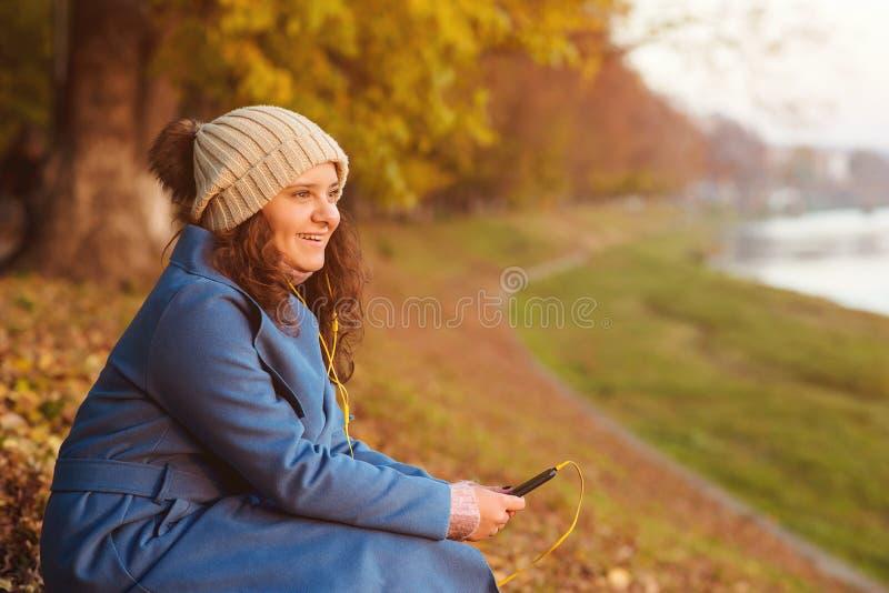 Ung attraktiv flicka som utomhus använder smartphonen Lycklig hipsterflicka som går i höstdag Den härliga flickan lyssnar musik p royaltyfri fotografi