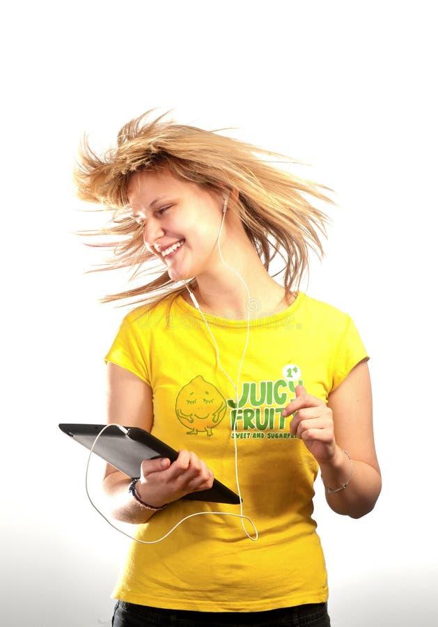 Ung attraktiv flickadans med en spelare mp3 arkivbild