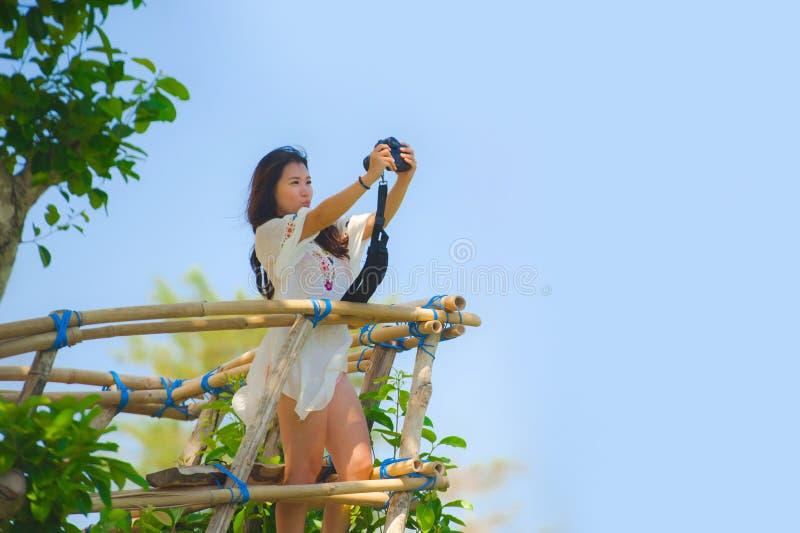 Ung attraktiv fotografkvinna som tar selfiefotoståenden med reflexkameran av det härliga landskapet med trädvegetation a royaltyfria foton