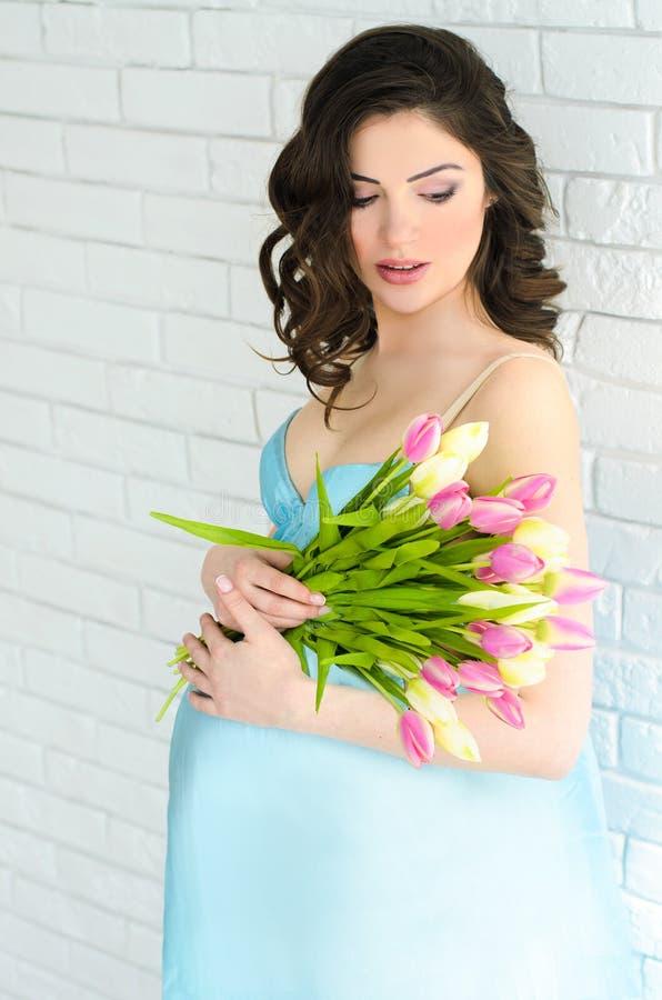 Ung attraktiv gravid kvinna med blommor arkivbilder