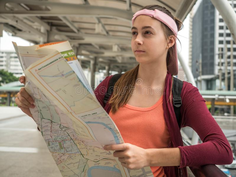 Ung attraktiv handelsresandekvinna som rymmer lägeöversikten i hennes händer, medan söka efter någon riktning på gatan, lopp elle royaltyfri fotografi