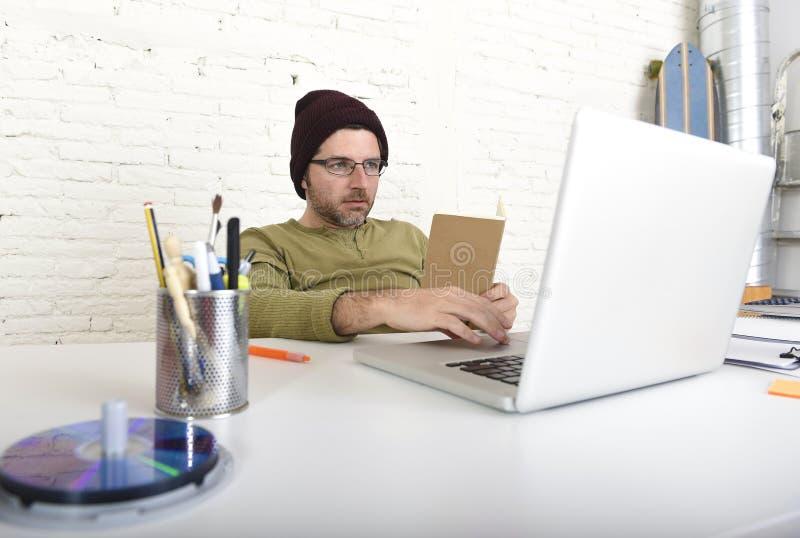 Ung attraktiv hipsteraffärsman som arbetar från hans inrikesdepartementet som självständig affärsmodell för freelancer royaltyfri fotografi