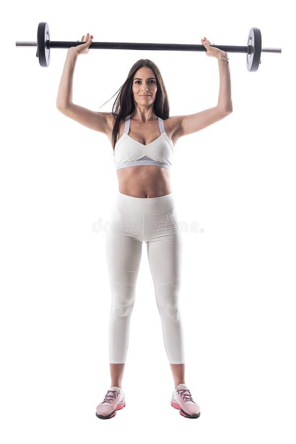 Ung attraktiv konditionkvinna som poserar, medan rymma skivstången över hennes huvud royaltyfria bilder