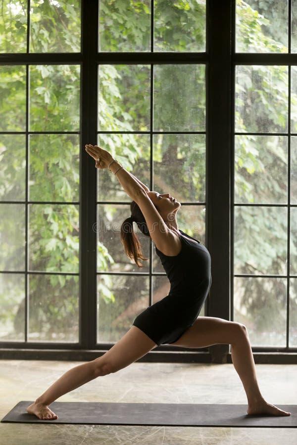 Ung attraktiv kvinna i övningen för krigare en, fönsterbackgroun royaltyfri foto